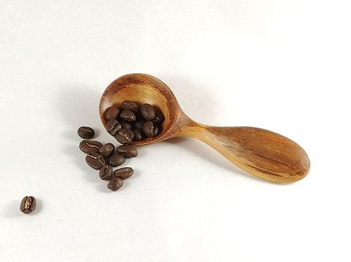 Short round-headed coffee scoop with multi-shaded wood grain. Shown with coffee beans