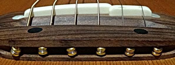 Insertion des cordes dans le chevalet d'une Guitare Folk