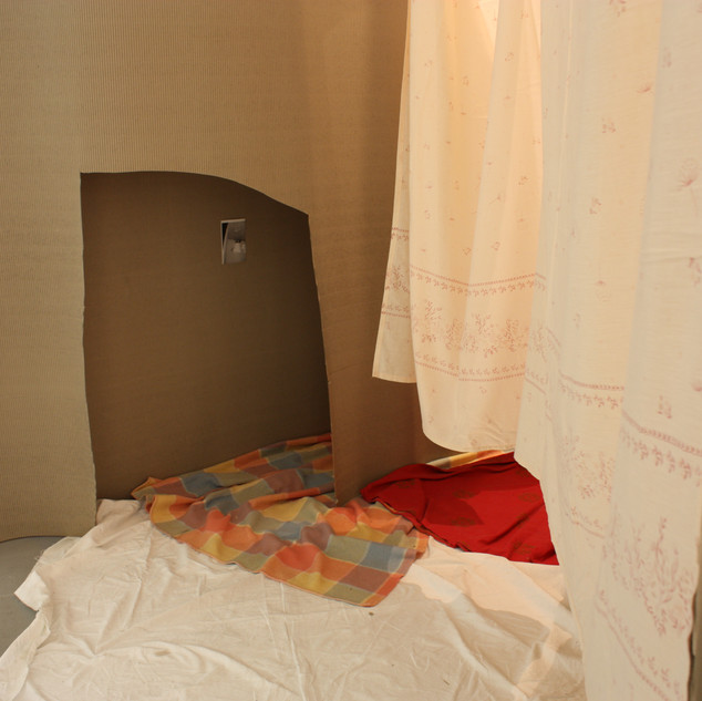 An entrance made of cardboard, blankets and sheets.