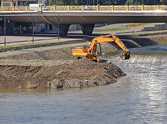 Excavator Machine Digging Levee at River