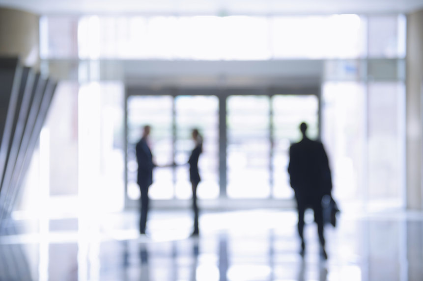 Image of three out of focus people walking through an office environment towards entrance doors