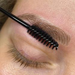 Microblading brushing the brow.