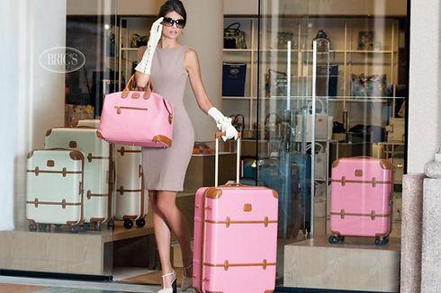 woman carrying brics pink luggage