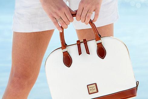 woman holding dooney and bourke handbag
