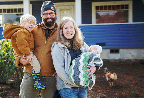 photo of a family of a smiling man, woman, and their two children in front of their house