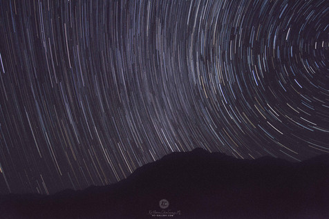 Star trails above mountains