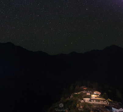 Night sky in the mountains above a school.