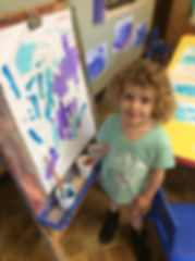 girl painting at easel.jpg
