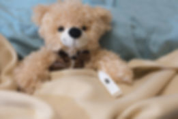 Teddy bear with a thermometer in bed.jpg