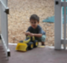 Toddler on the preschool playground with a truck.