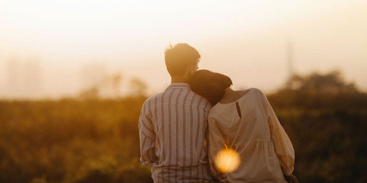 couple sitting in sunset - gottman method of therapy