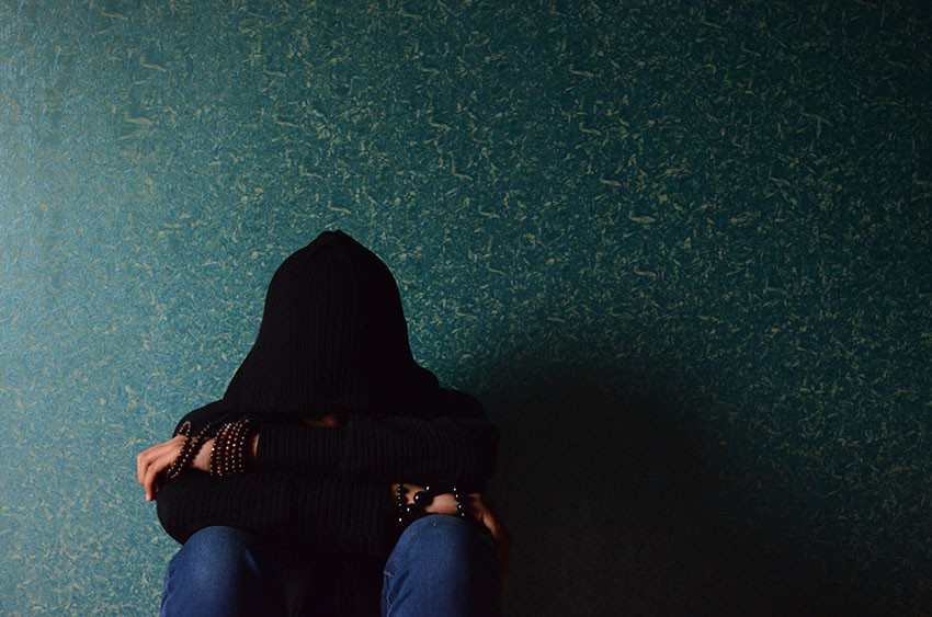 woman sitting in darkness - covid19 and mental health