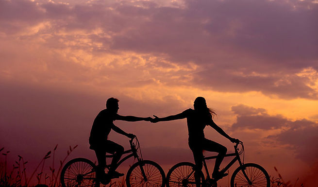 man and woman couple holding hands while riding bikes - couples therapy