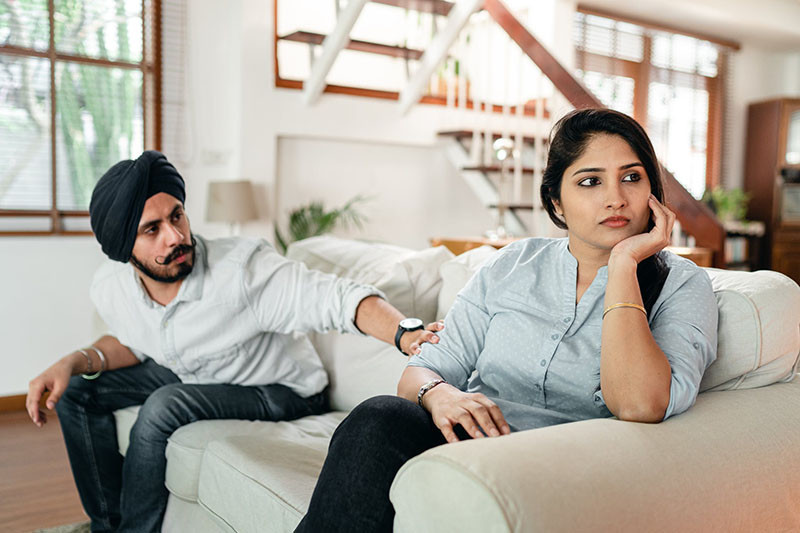 couple arguing on couch at home