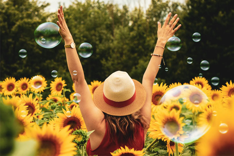 woman in sunflowers and bubbles - achieve happiness