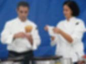 A man holds a sweet crêpe as a woman beside him folds a napkin.