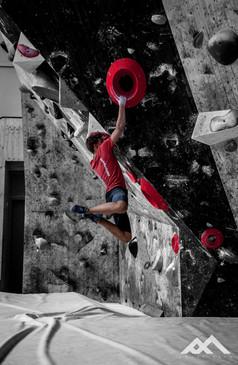 Junger Mann, der eine dynamische Kletterbewegung macht