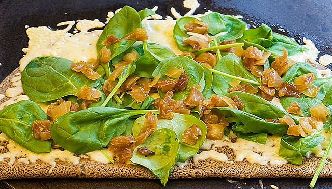 An open-face buckwheat crêpe with cheese, spinach, and carmalized onions.
