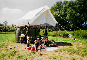 As a Girl scout, by our tent which lays on a wood structure that we built ourselves with only ropes and wood that we cut in the forest