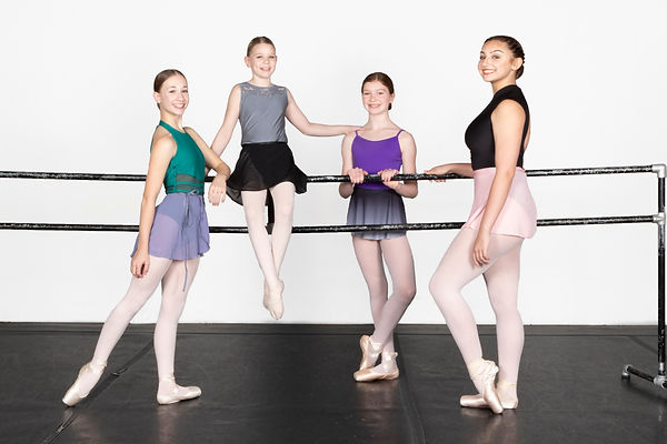 Four student company dancers pose arranged around a ballet barre, smiling at the camera.