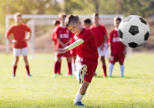 Boy kicking football on the sports field during soccer match.jpg