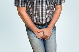 Man with hands holding his crotch, he wants to pee - urinary incontinence concept