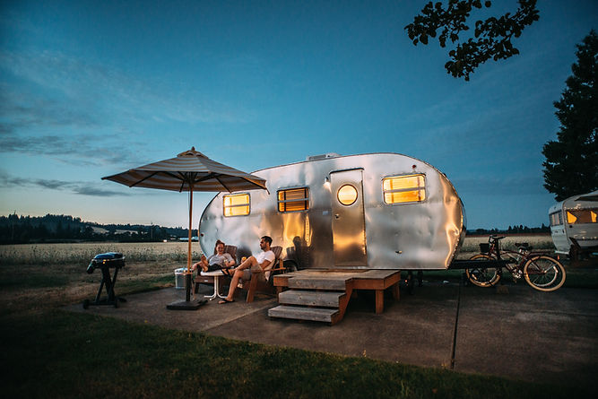 Small rounded Airstream travel trailer with a couple enjoying the sunset