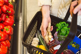 Woman grocery shopping. Grocery basket is full of vegetables and herbs.