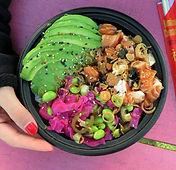 A salmon poke bowl with green avocado, bright pink pickled red cabbage, edamame, and fried shallots held over a pink table by a woman's hand with red nail polish.