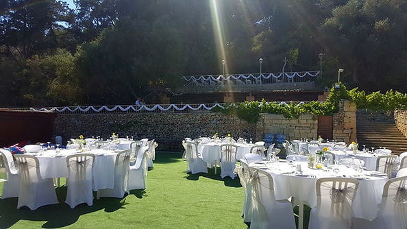 seated wedding with round tables in a summer garden