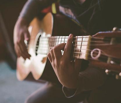 Close Up of a man strumming the guitar