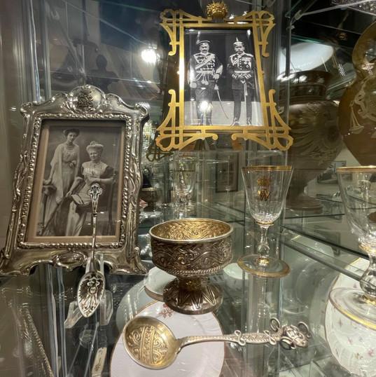 Saltkar med skje i dragestil (830S) utformet av Henrik Møller i Trondheim ca. 1900. Har monogrammet til Keiseren (WR) inngravert og vært i hans private besittelse. Rammen i bakgrunnen med den russiske krone var en personlig gave fra Tsar Nicholas II.