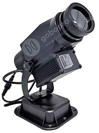 Светодиодный гобо проектор с защитой от пыли и влаги IP65? а также с функцией вращения изображения на 360°. Можно использовать для уличной рекламы и проекции изображений и логотипов. Не боится дождя и снега. Подвижная картинка гарантирует дополнительное внимание к Вашему логотипу или рекламе.  Управление проектором производится с помощью входящего в комплект пульта ДУ. В качестве источника света используется светодиод CREE мощностью 15 Вт, сочетающий в себе экономичность и способность обеспечивать достаточную яркость проецируемого изображения. Оптическая система проектора, разработанная в Японии, обеспечивает четкость картинки. Широкие возможности по фокусировке изображения позволяют использовать проектор на расстоянии от 1 до 10 метров. Ваш логотип или картинка печатаются на специальном закаленном стекле. Возможна полноценная цветная (фото) печать.