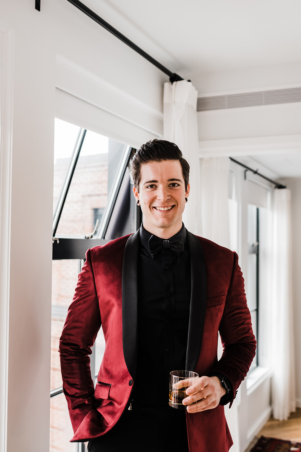 Groom wearing a burgundy jacket and black pant combo for his tux