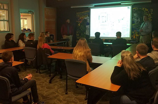 High school students watching an on screen presentation while sitting in a classroom listening intently to a professional engineer give a presentation