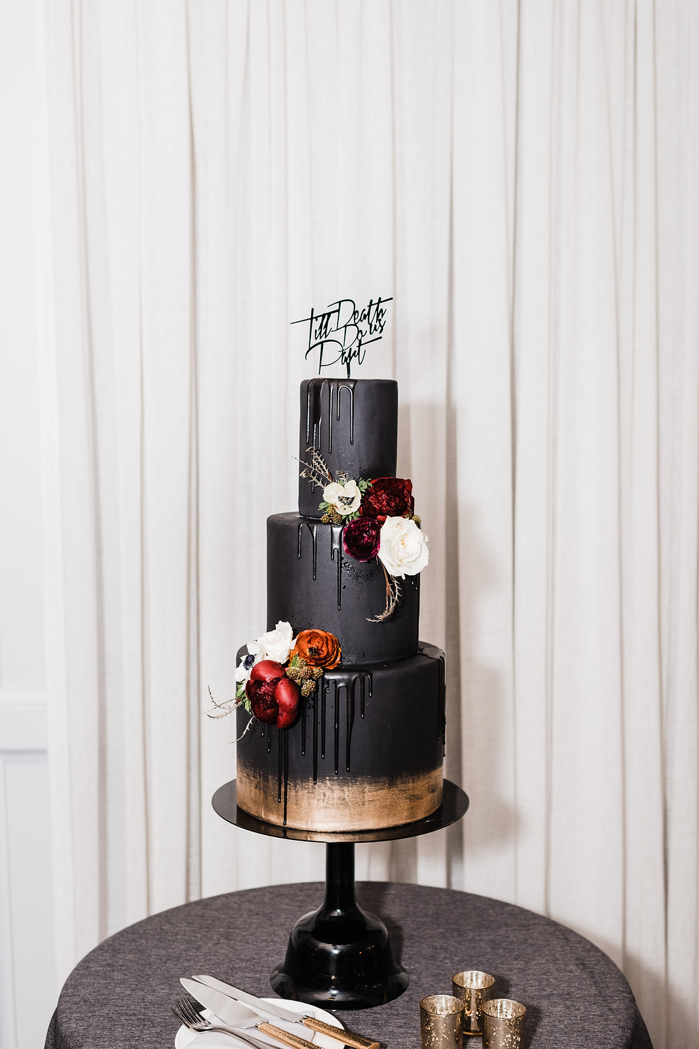 Black three tier wedding cake decorated with ivory and burgundy flowers
