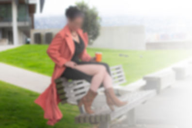 Bella sitting on the top of a park bench wearing along black dress wth a peach coat over the top. She is seductively pulling up the side of the dress to expose her leg