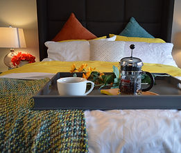 Hotel bed with a breakfast tray on the edge (end)