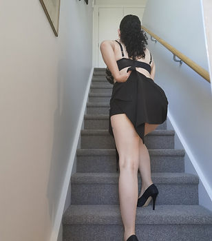 Selfie image of bella walkng up a flight of stairs, her back is to the camera and she is pulling up her skirt, on top she is wearing only a black bra
