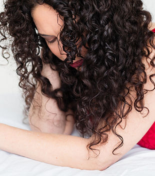 Bella lying on her chest, with her head propped up by her right arm, wearing red lingerie