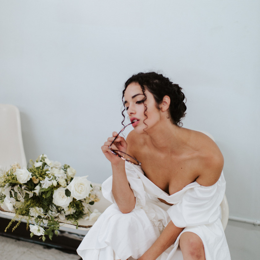 Girl in two piece wedding dress hunched over, with sunglasses in her mouth looking into the distance