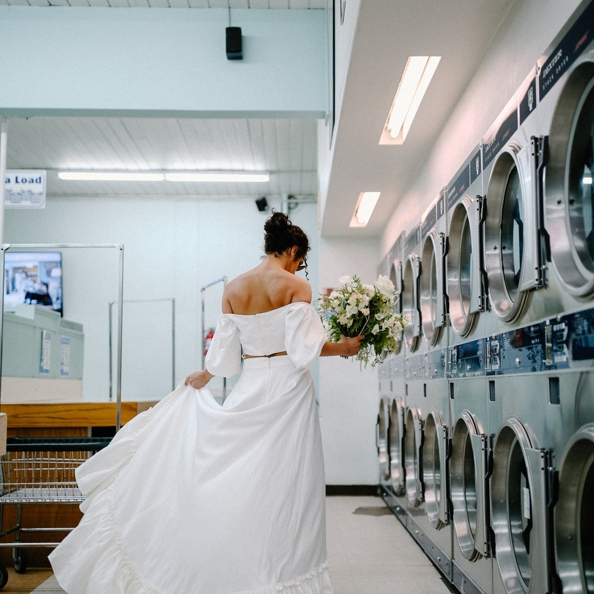 Bride with bouquet at a laundromat walking away from the camera and spinning