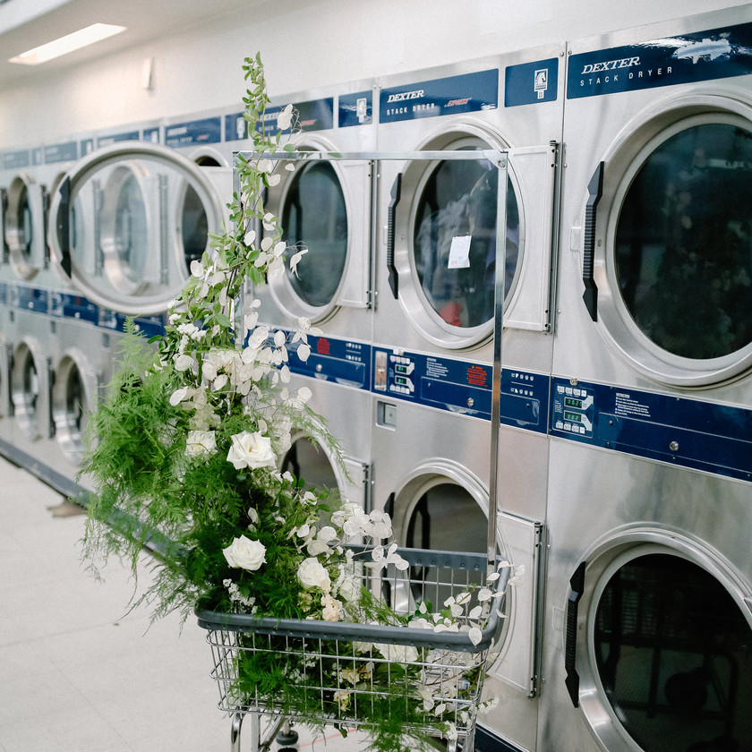Washing machines and dryers at a laundromat with wedding florals on a laundry cart