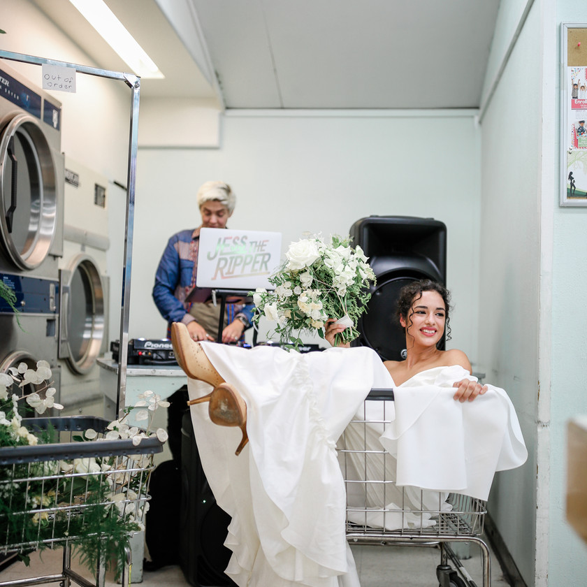 Happy smiling bride with heels sticking out of the laundry cart she's sitting in, DJ behind her playing music Jess the Ripper