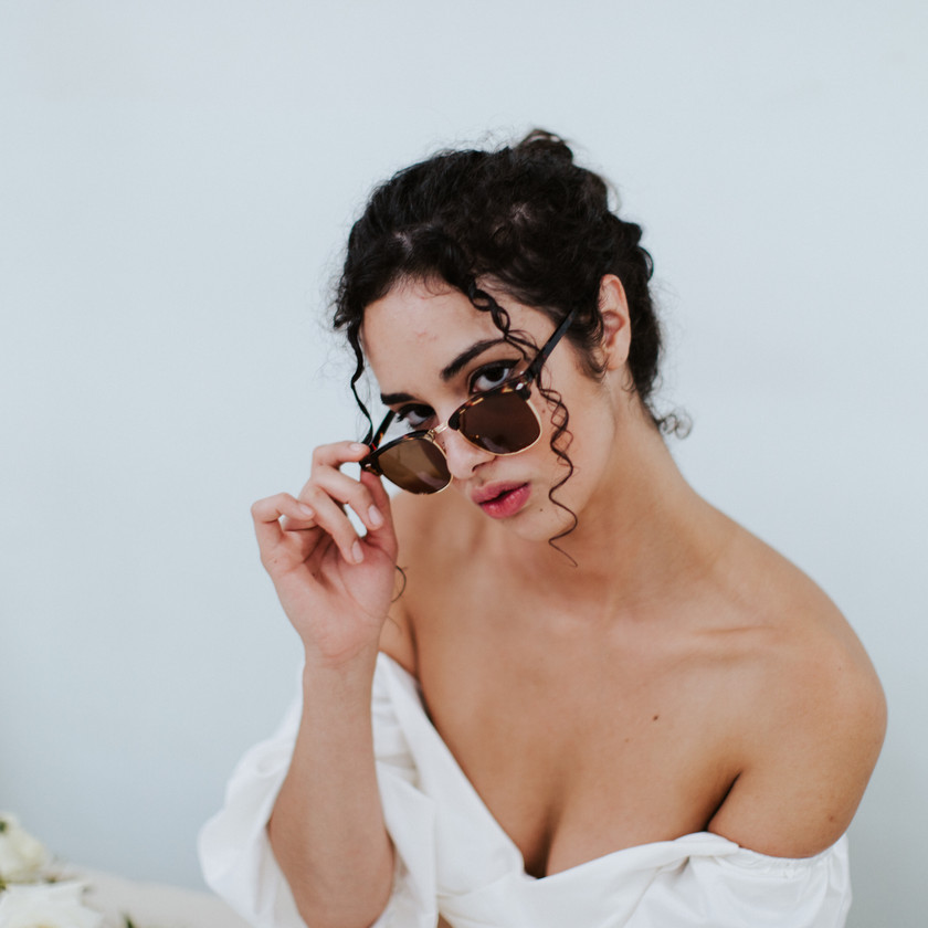 Girl in off shoulder white top holding sunglasses down looking out the top