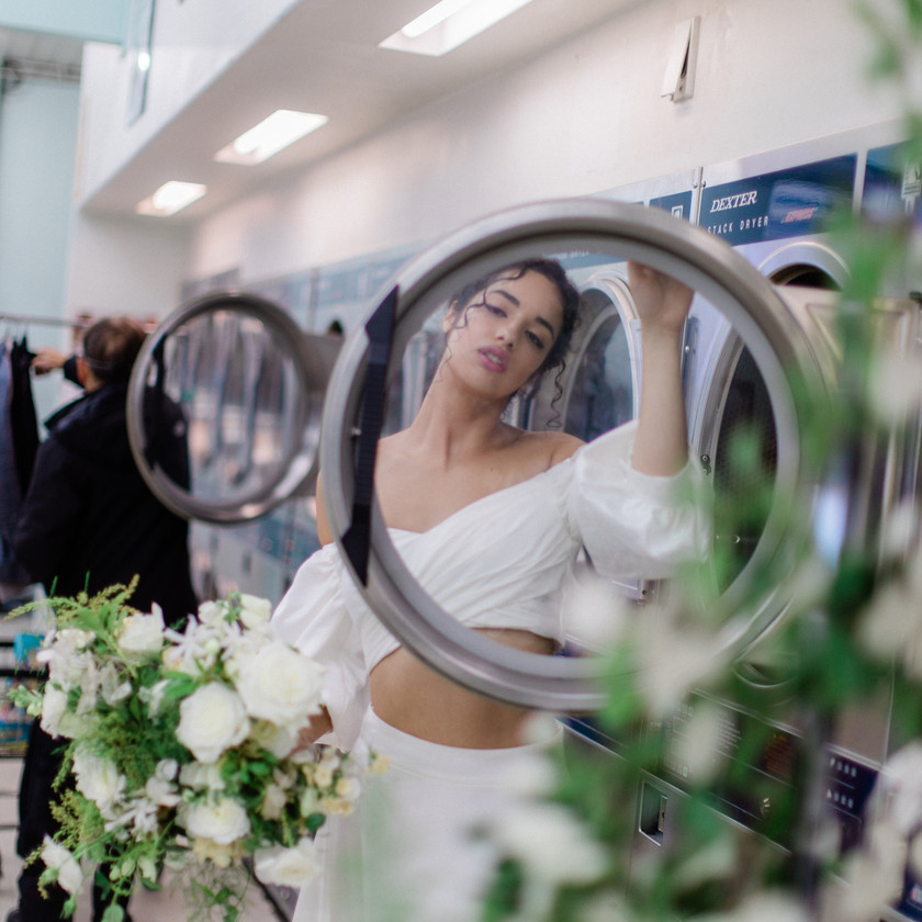 Bride in two piece Eleanor's Bridal white off shoulder wedding dress looking through washing machine at laundromat