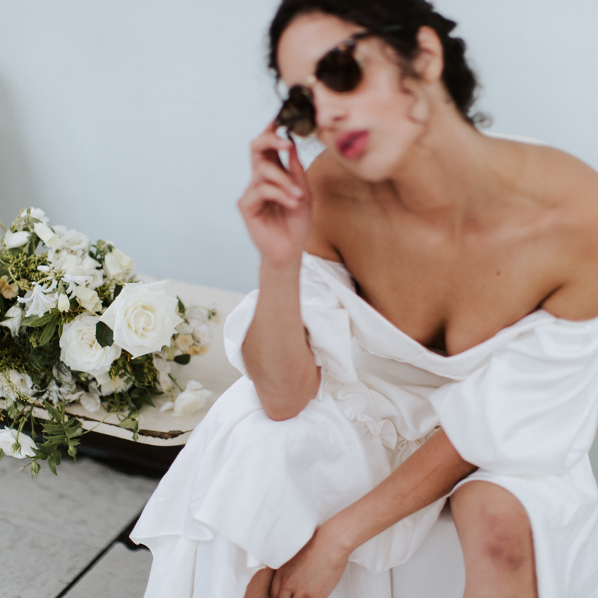 Bride seated against a wall wearing sunglasses and off the shoulder wedding gown white, hunched over