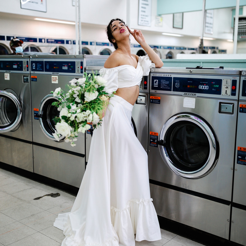 Full view of brides two piece off shoulder satin wedding gown, leaning against an industrial washing machine holding bridal bouquet
