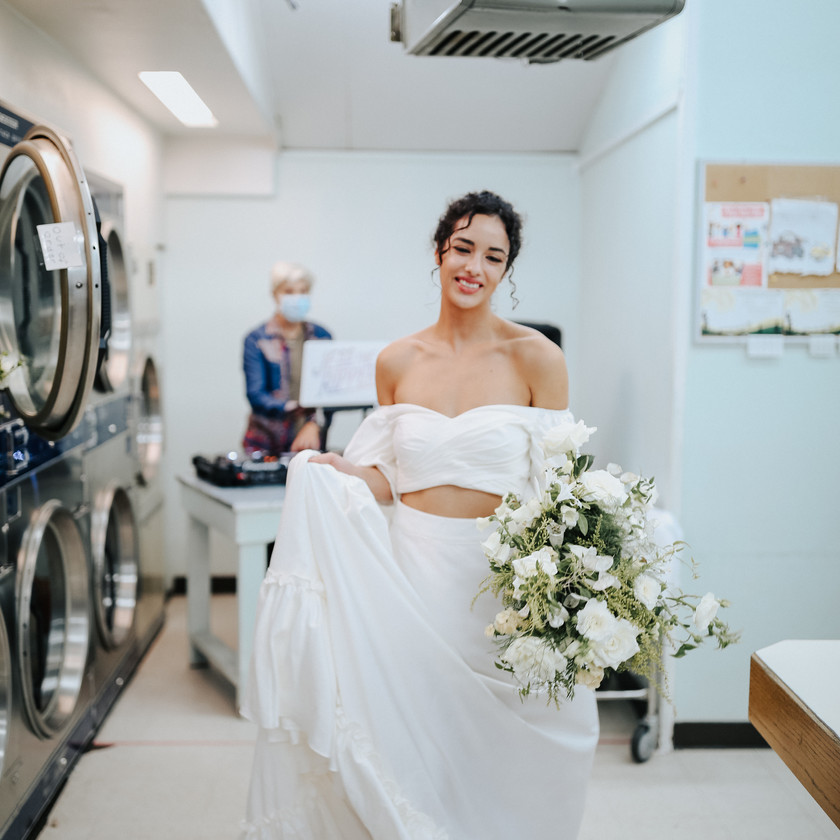 Bride holding her long train satin wedding gown and smiling with her eyes closed, holding a wedding bouquet at a laundromat