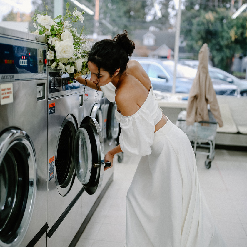 Bride doing her laundry at a laundromat in a two piece white wedding dress holding bouquet